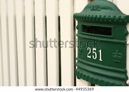 green mailbox on cream white picket fence - stock photo