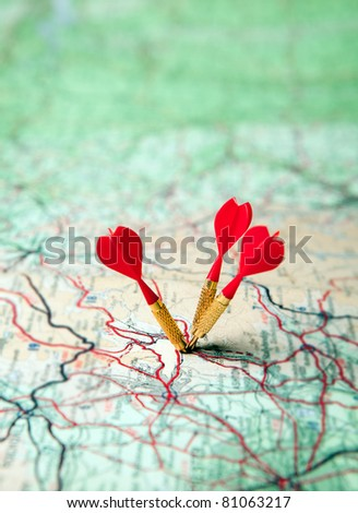 Green map with three red darts - shallow focus - stock photo