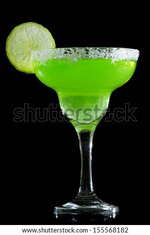 green margarita isolated on a black background served with a thick salt rim - stock photo