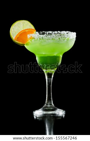 green margarita isolated on a black background served with a thick salt rim and a lime and orange on the rim - stock photo