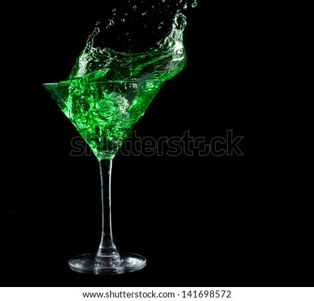 green martini cocktail splashing into glass