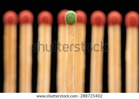 Green match standing in front of defocused set of eight red wooden matches, isolated on black background - stock photo
