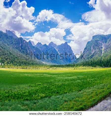 Green meadow and blue sky with clouds over the mountains Ukraine. - stock photo