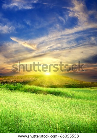 Green meadow and bright sky during sundown. - stock photo