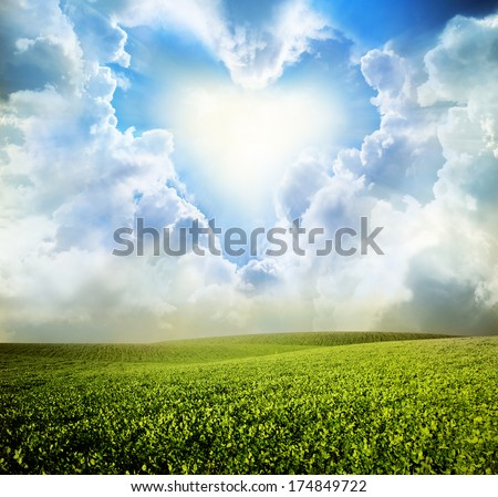 Green meadow under blue sky with heart clouds - stock photo