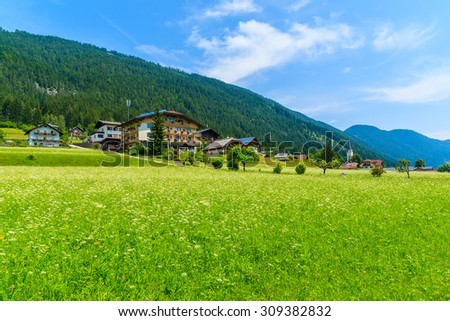 Green meadow with flowers with traditional countryside houses in background, Weissensee lake, Alps Mountains, Austria - stock photo