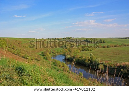 Green meadow with river and hills. Beautiful nature landscape - stock photo
