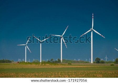 green meadow with Wind turbines generating electricity  - stock photo
