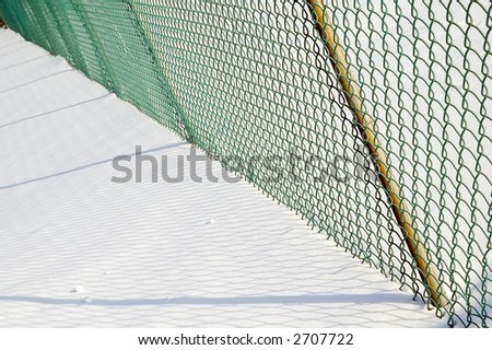 Green mesh fence and shadows on snow