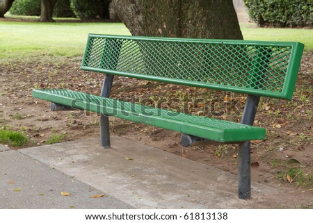 Green metal bench with trees and grass in background