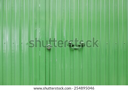 Green metal door, detail of a closed door, protection and decoration - stock photo