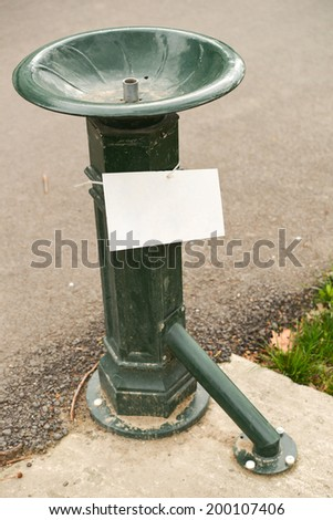 green, metal public water fountain in a park. copy space - stock photo
