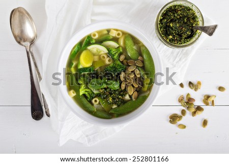 Green minestrone with a lot of vegetables and pasta - stock photo