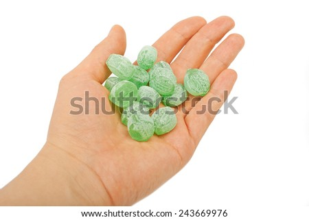 Green mints candy  in hand isolated on white background. - stock photo
