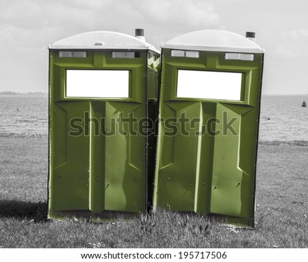 Green mobile toilet on a black and white beach with two pure white blank cells  - stock photo