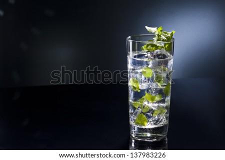 Green Mojito cocktail in disco light setting - stock photo