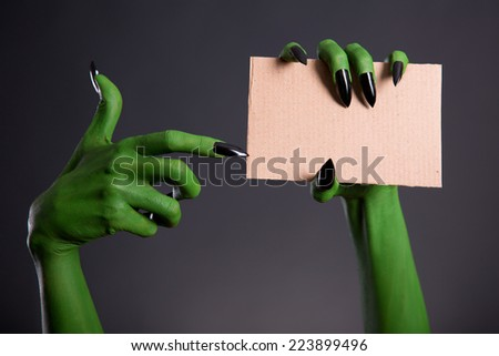 Green monster hand with black nails pointing on blank piece of cardboard, Halloween theme   - stock photo