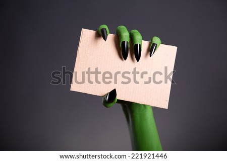 Green monster hand with sharp nails holding blank piece of cardboard, Halloween theme   - stock photo