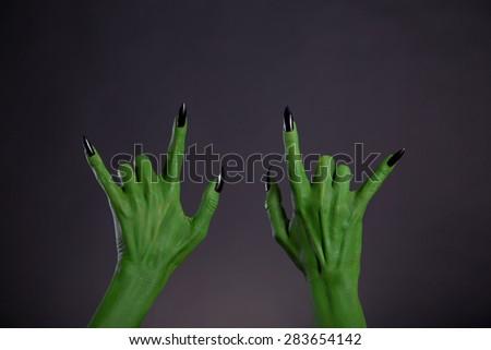 Green monster hands showing heavy metal gesture, Halloween theme   - stock photo