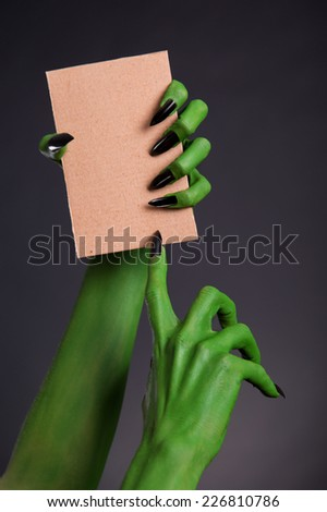 Green monster hands with black nails holding blank piece of cardboard, Halloween theme   - stock photo