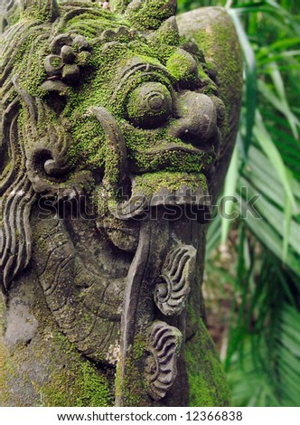 Green moss on menacing stone carving - stock photo