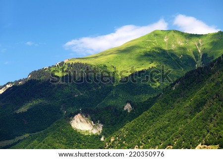 Green mountain with woods on hillside, summer landscape in sunny day - stock photo