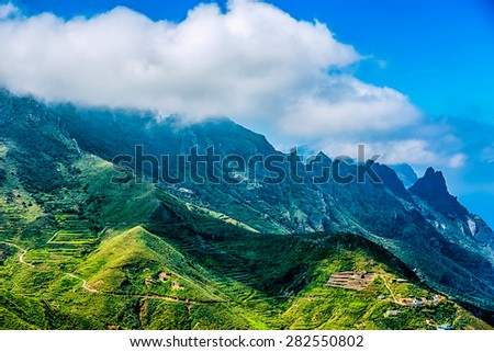 Green mountains or rock with clouds over peak and blue sky