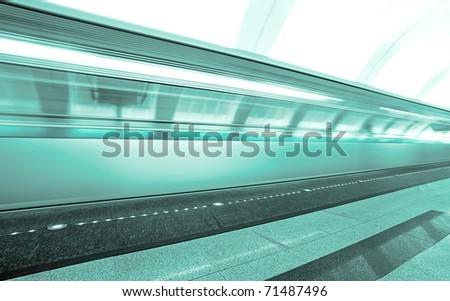 green moving train on underground platform - stock photo