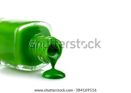 green nail Polish in the bottle and a little bit spilled on a white isolated background - stock photo