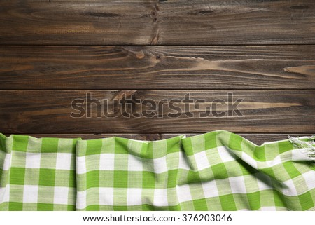 Green napkin on the old wooden table. - stock photo