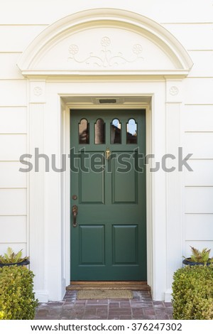 Green narrow front door with white siding, closeup