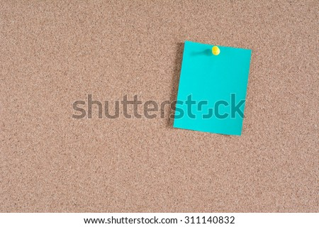Green note paper on cork board background