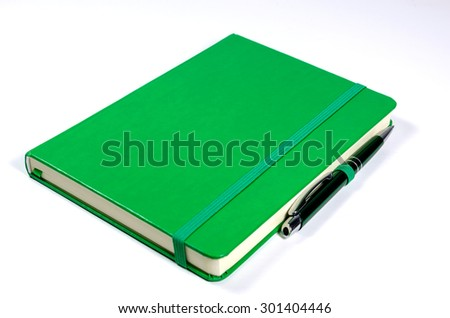 Green notebook and pen isolated on white background - stock photo