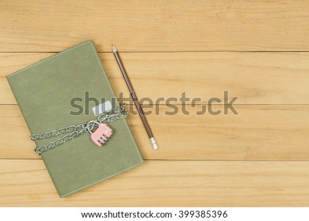 green notebook locked by chain and pink padlock on wooden background,safety privacy data concept - stock photo