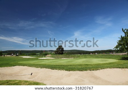 green of a beautiful golf course surrounded with bunkers with dramatic summer sky - stock photo