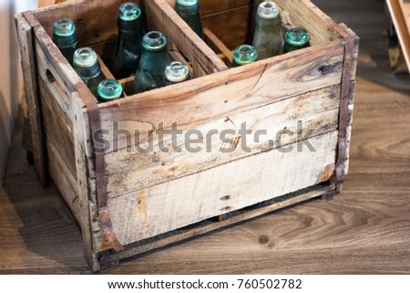 Green old bottles are in the old wooden crate. Selective focus.