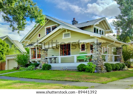 Green old craftsman style home with covered porch in the summer. - stock photo