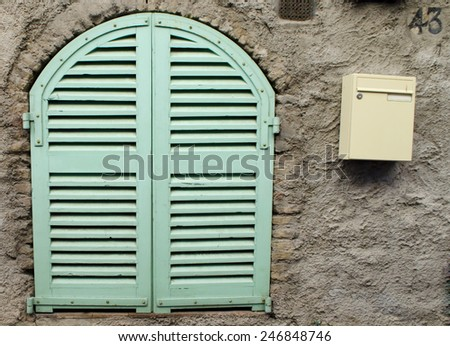 Green old style wooden blinds with a mailbox on the ancient cement wall - stock photo