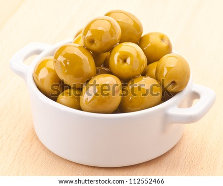 Green olive oiled in white porcelain bowl - stock photo
