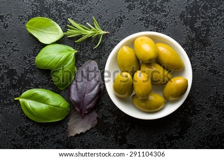green olives and herbs on black table - stock photo