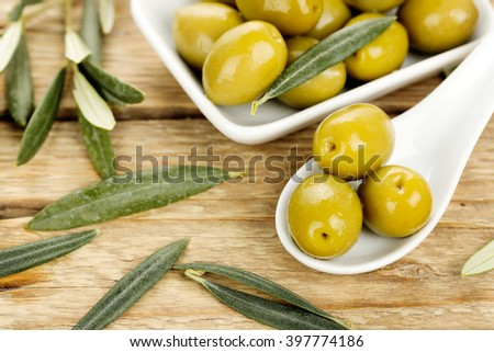 green olives and leaves on old wooden surface