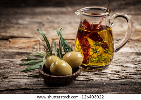 Green olives and olive oil with spice - stock photo