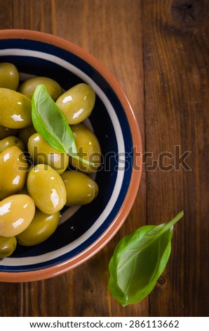 Green olives in a ceramic bowl on wooden background - stock photo