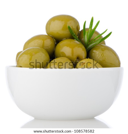 Green olives in a white ceramic bowl on white background. - stock photo
