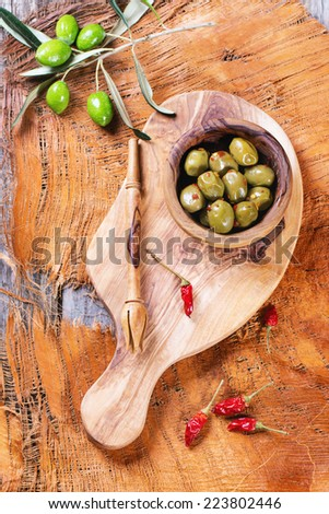 Green olives in olive wood bowl with chili pepper and olive's branch served on cutting board over wooden table. Top view. - stock photo