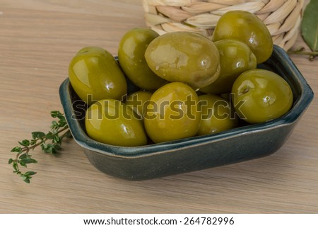 Green olives in the bowl with thyme branch  - stock photo