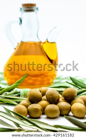 Green olives,  olive oil and olives leaves on a white background - stock photo