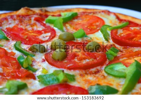 Green olives on a pizza with tomatoes, cheese and sweet (bell) pepper, shallow DOF - stock photo