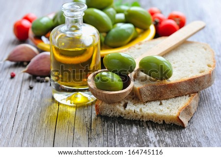 Green olives on a wooden spoon on a slice of bread - stock photo