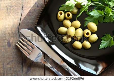 Green olives on black plate near fork and knife on wooden table - stock photo